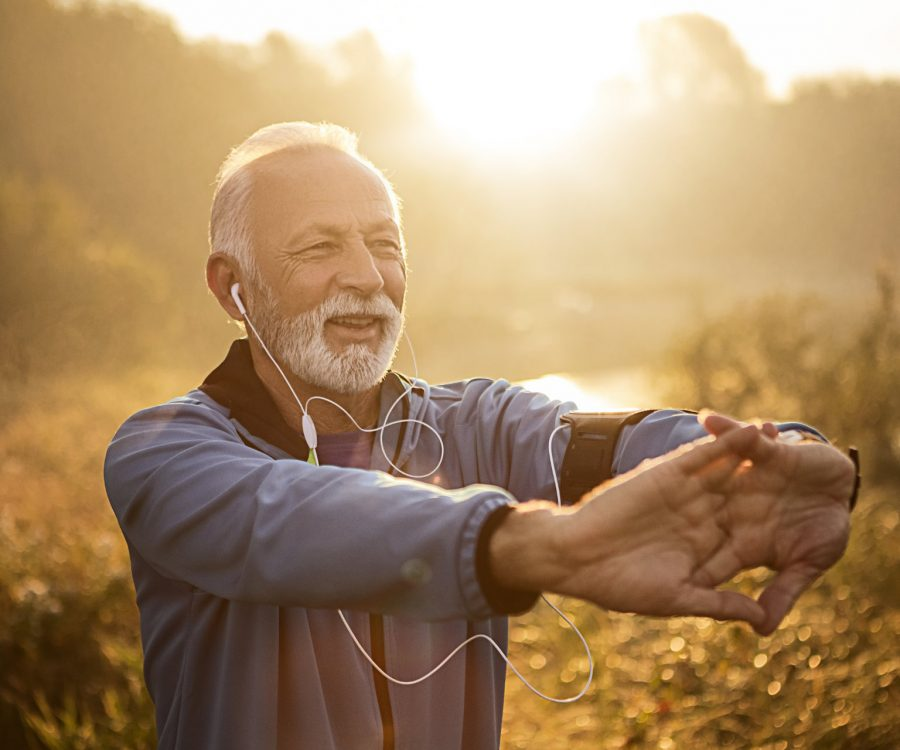 Senior jogger by lake in morning time with outstretched hands